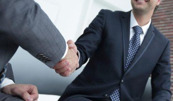 Criminal defense attorney in Irvine shaking hands with a man charged with a white collar crime