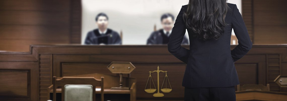 An attorney stands in front of two judges