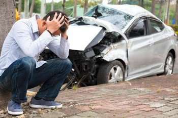 Man crouched near a wrecked car in need of a vehicular manslaughter lawyer in Orange County, CA