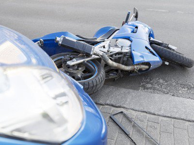 Motorcycle on the ground after being hit by a car