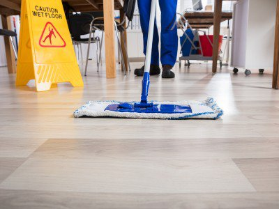 Wet floor sign sitting on an area currently being mopped