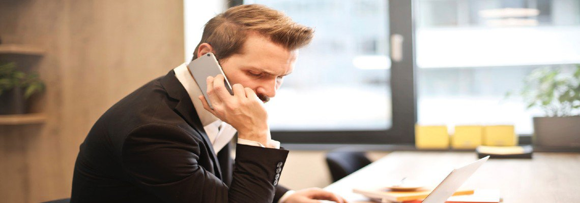 Businessman speaking on the phone in front of his laptop