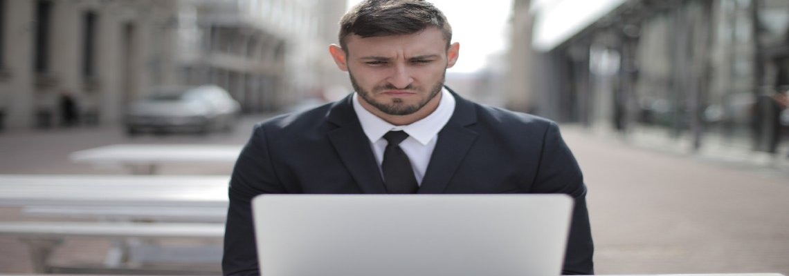 Business man frowning at his laptop
