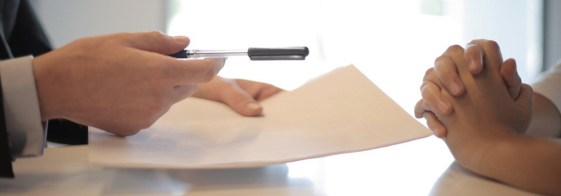 Pen and paper being handed off to someone