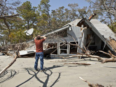 Distraught man looking at a destroyed home