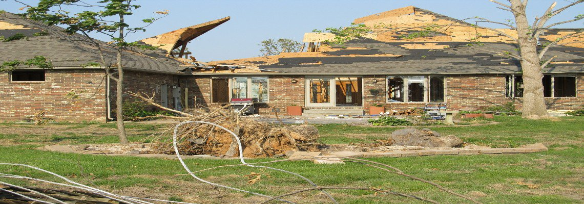 Home damaged by a tornado with debris in the yard