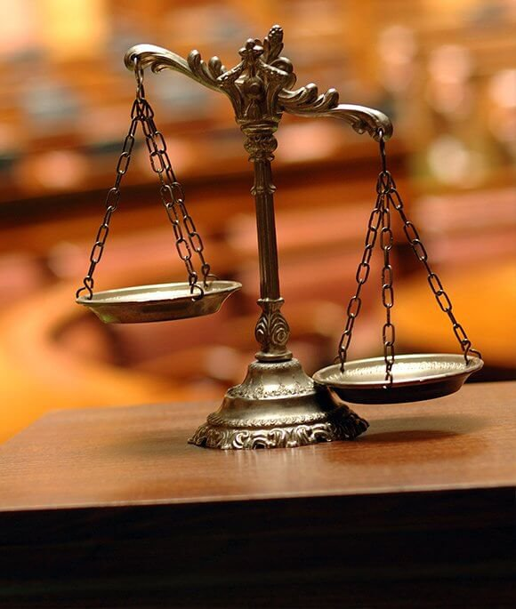 Scales of justice on wooden desk