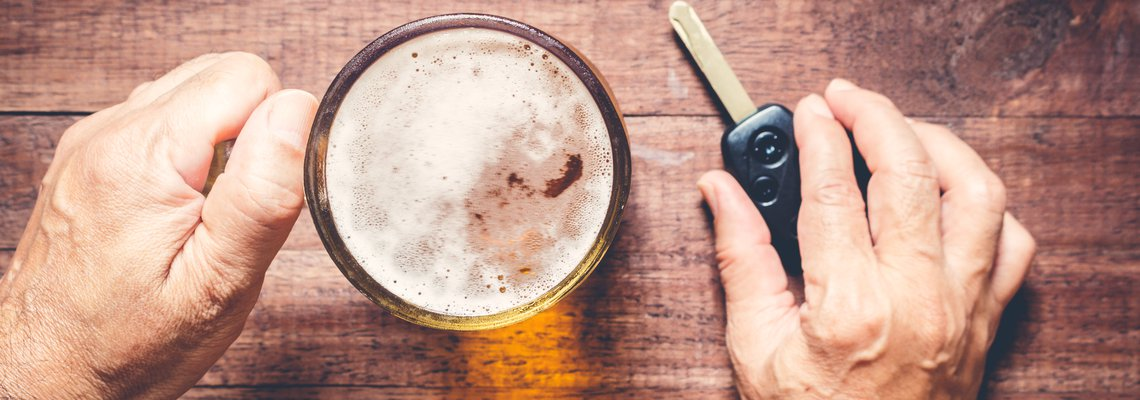 A man holding a beer in one hand and car keys in the other