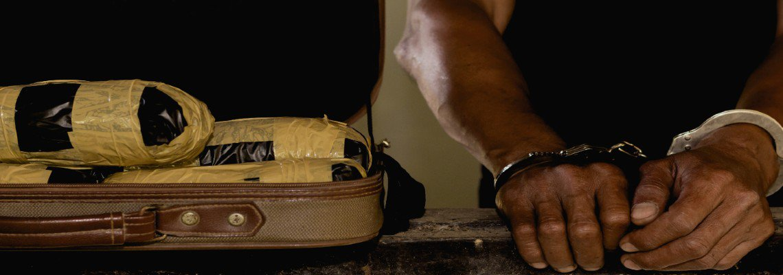 Handcuffed man next to suitcase full of drugs