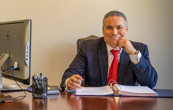 Attorney Thomas Michaelides sitting at his desk smiling