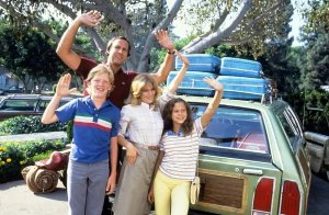 Family of Four Waving goodbye in front of a packed car