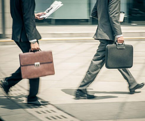 Businessmen walking with briefcases