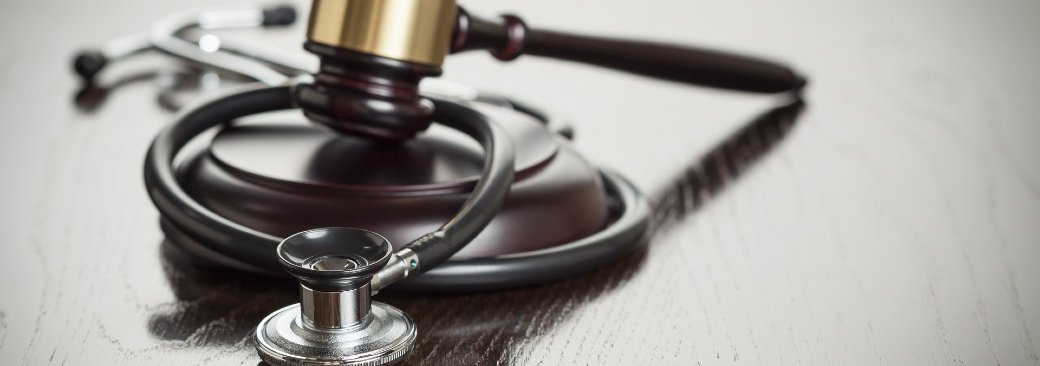 Stethoscope and gavel on wooden surface