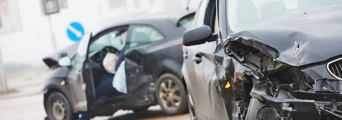 Close up of a two-car accident with one driver sitting in the driver seat with the door open