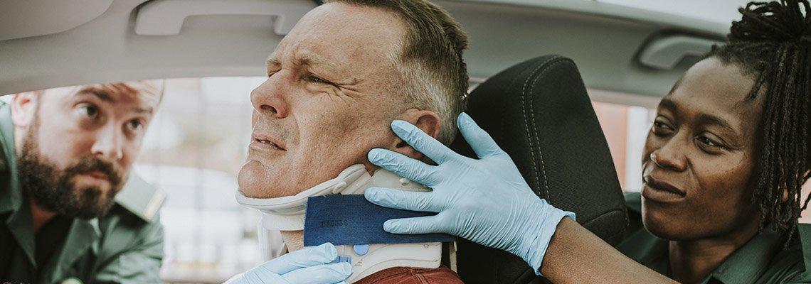 A man has a neck brace put on by an emergency responder