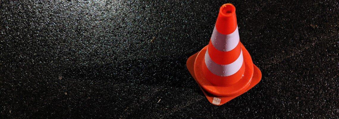 Traffic cone on black pavement
