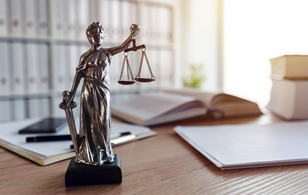 Lady justice holding scales sitting on a desk