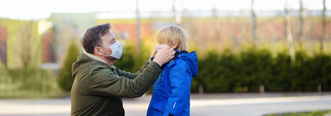 Man wearing a protective mask puts a face mask on a his son
