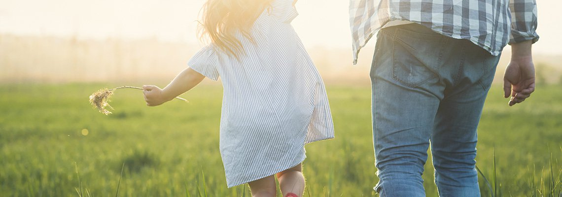 A father and daughter play in a field