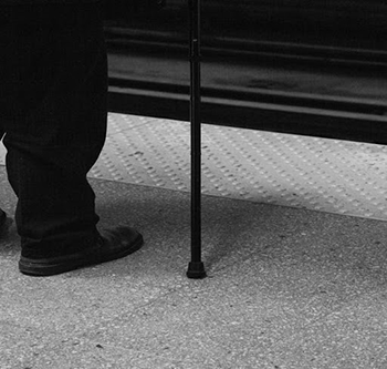 Black and white image of man waiting for the bus