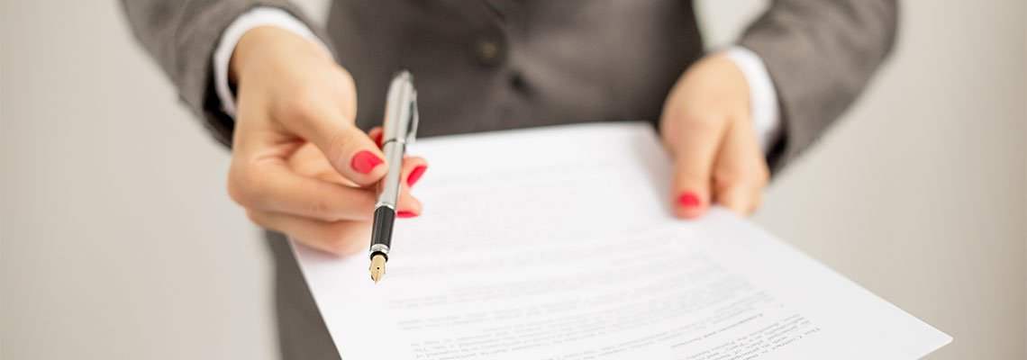 Woman offering a pen to sign document