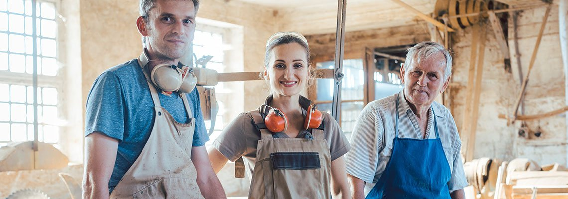 A father stands with his two adult children in their workshop