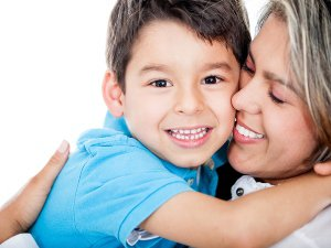 Affectionate mother and son hugging and smiling