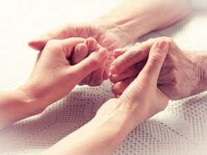 Younger hands holding the hands of an elderly person