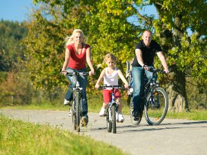 Parents and child riding bikes