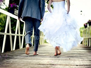 Newlywed couple walking barefoot on a bridge