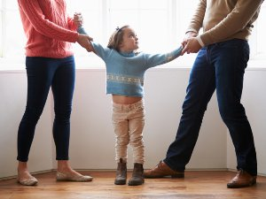 A couple holding the arm of their daughter appearing to be arguing over the child