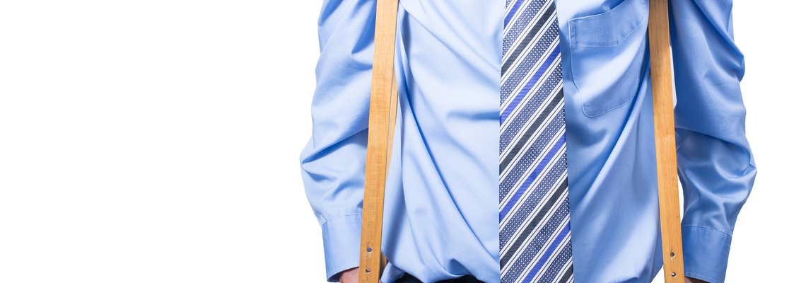 Businessman standing in crutches