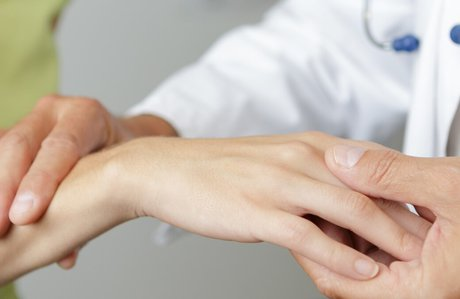 Doctor examining a woman's hand and wrist