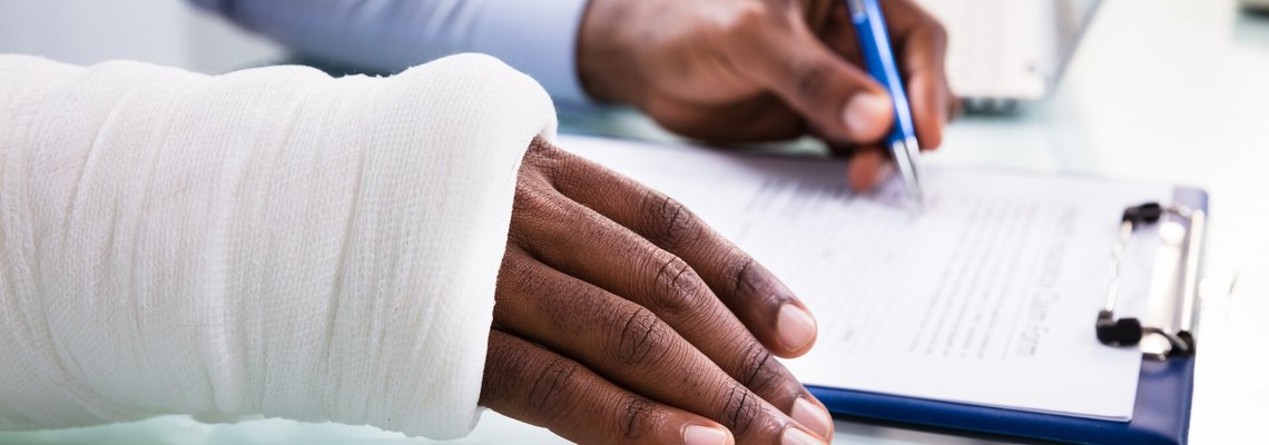 Injured person signing some documents with a cast on their wrist