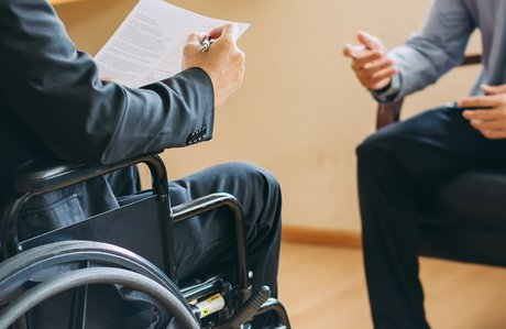Injured person in wheelchair discussing disability with attorney