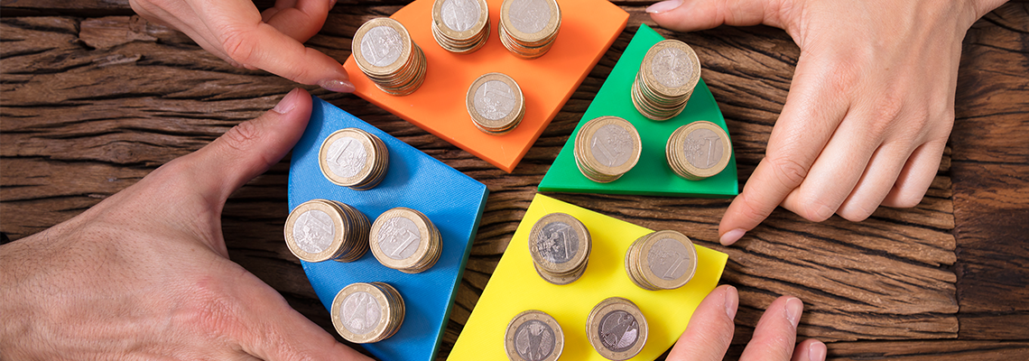 Businesspeople Stacking Coins On Pie Chart