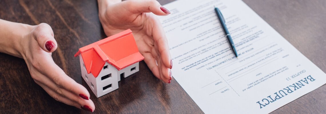 Hands around a tiny house with a bankruptcy form and pen nearby