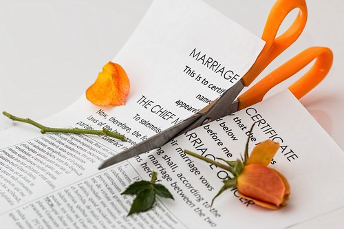 Scissors cutting marriage certificate and rose