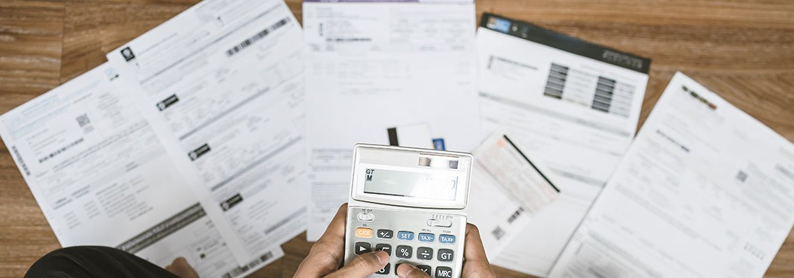 Finical documents on the ground, someone holding a calculator