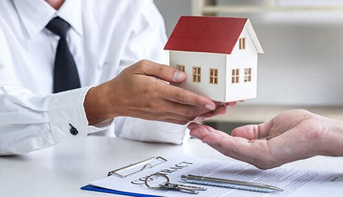 A business person passing a tiny model home into a property owner's hand; a contract, set of keys, and pen are on the table