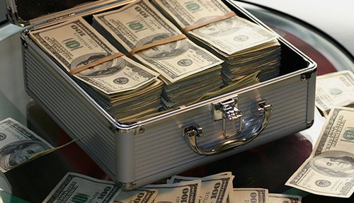 An open metal briefcase full with stacks of 100 dollar bills