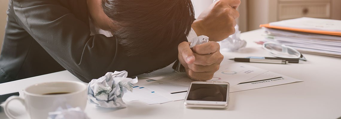 Frustrated man with his head on a desk surrounded by crumpled paper