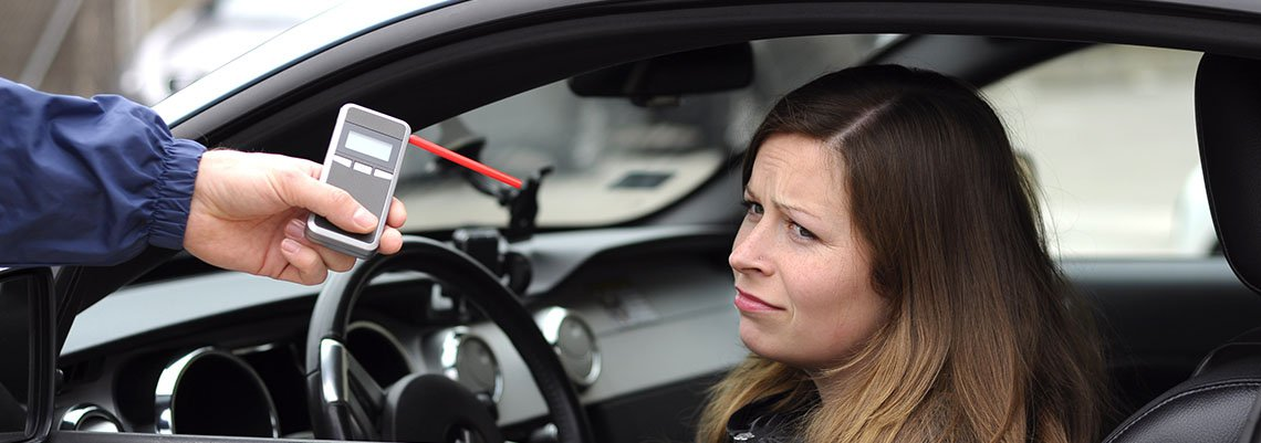 Woman making a face at a breathalyzer in a car