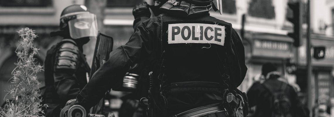 black and white photo of police in riot gear