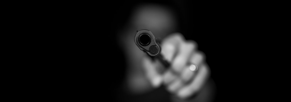 black and white picture of person holding a gun
