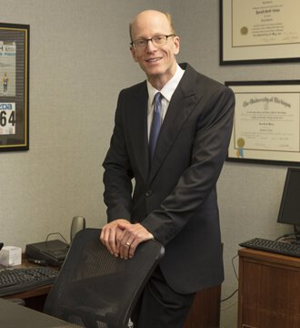 Attorney Ronald Weiss standing behind desk