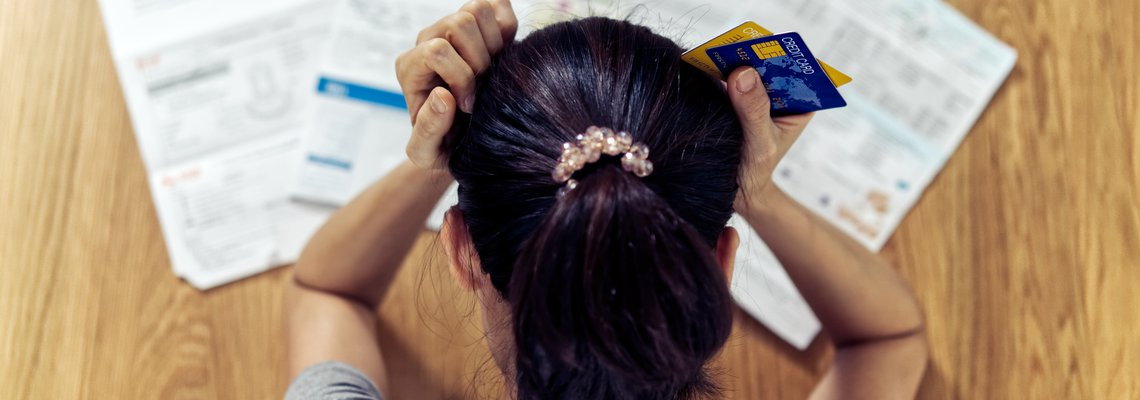 Young woman holding her head in her hands while staring at a stack of credit card bills