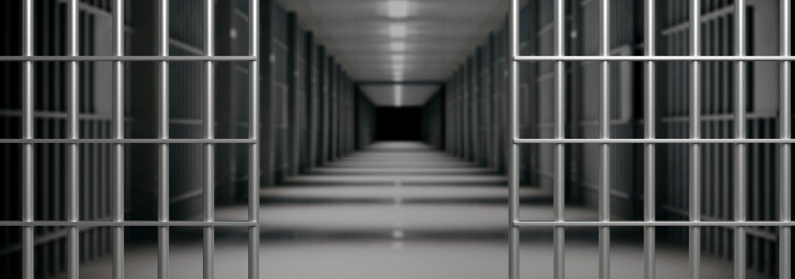 An open jail cell and a hallway of cells