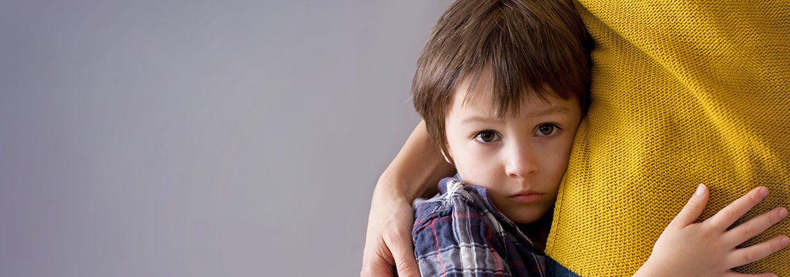 Child worried and hugging an adult
