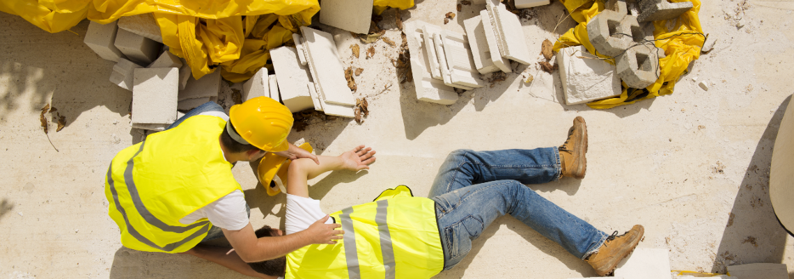 Two workers on a construction site, one kneeling down to check on the other after an injury
